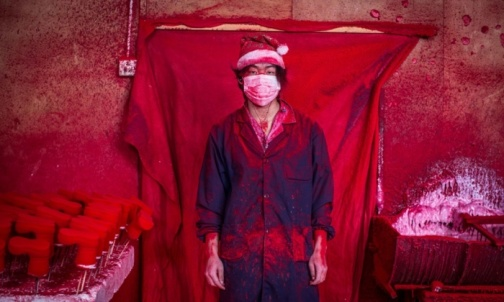 Santa's workshop … 19-year-old Wei works in a factory in Yiwu, China, coating polystyrene snowflakes with red powder
