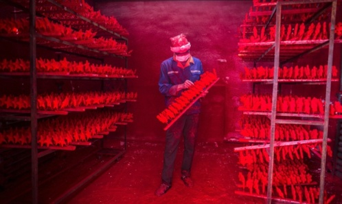 The two men produce 5,000 red snowflakes a day, and get paid around £300 a month